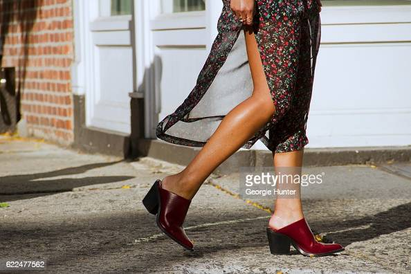 Tina Maria Tran wearing red and black sheer floral midi dress with high slits from Rat Boa and red slip on leather mules shoes with low heel and...