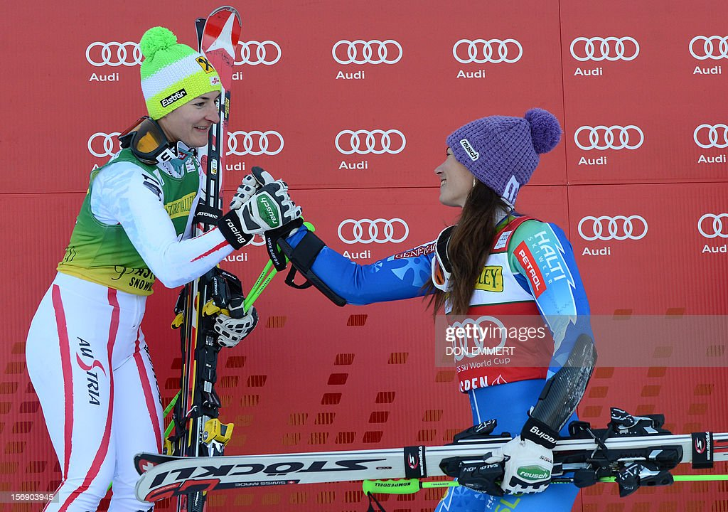 Tina Maze (R) of Slovenia shakes hands with third-placed Austrian Kathrin Zettel on the podium after winning the women's World Cup giant slalom in Aspen on November 24, 2012. AFP PHOTO/Don EMMERT