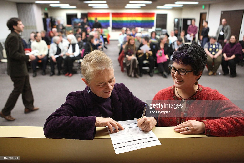 Tina Roose, of Olympia, left, signs an application for a marriage license as her partner, Teresa Guarjardo, looks on during ceremonies to give out marriage licenses at the Thurston County Courthouse shortly after midnight on Thursday, December 6, 2012.