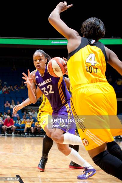 Tina Thompson of the Los Angeles Sparks drives past Amber Holt of the Tulsa Shock during the WNBA game on August 21 2011 at the BOK Center in Tulsa...