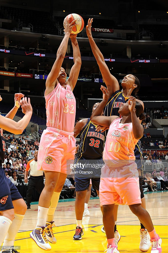 Tina Thompson of the Los Angeles Sparks goes to the basket against Tammy SuttonBrown of the Indiana Fever as Sparks teammate Andrea Riley looks on...