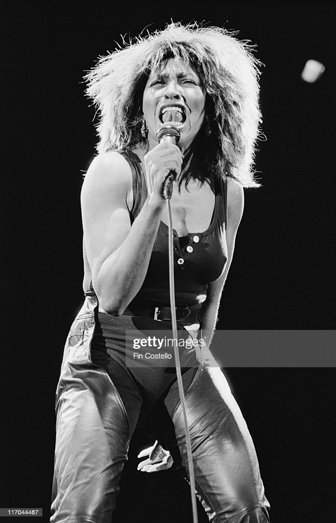 Tina Turner, US singer, singing into a microphone on stage during a live concert performance in Helsinki, Finland, circa 1985.