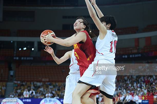 Ting Shao of China tries to shoot while Ramu Tokashiki of Japan competes in finals match between Japan and China during the 2015 FIBA Asia...