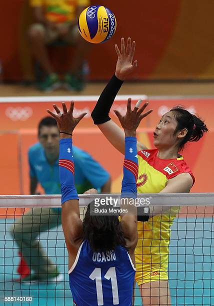 Ting Zhu of China spikes the ball against Karina Ocasio of Puerto Rico during the women's qualifying volleyball match between the China and Puerto...