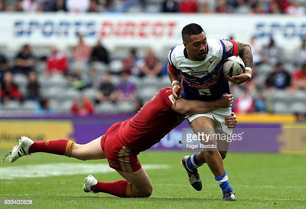 Tinirau Arona of Wakefield Wildcats tackled by Glenn Stewart of Catalans Dragons during the First Utility Super League match between Wakefield...