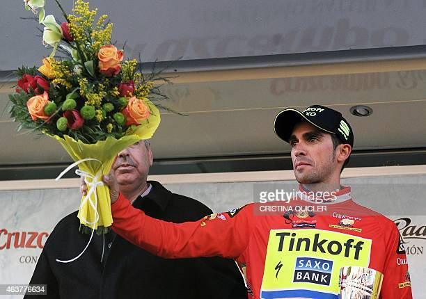 TinkoffSaxo's Spanish cyclist Alberto Contador raises a bouquet of flowers on the podium after winning the first stage of the 61 Vuelta a...
