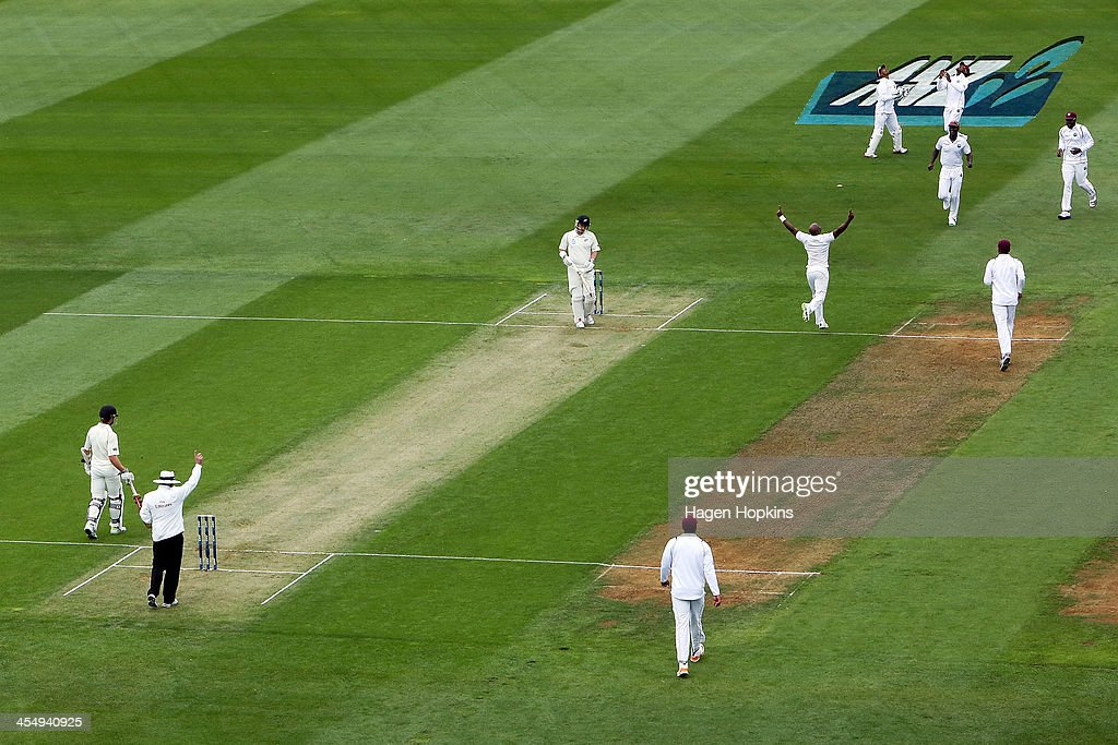 Tino Best of the West Indies celebrates after taking the wicket of Hamish Rutherford of New Zealand during day one of the Second Test match between...