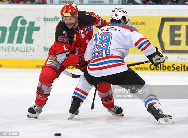 Tino Boos of Hanover and Greg Leeb of Nuernberg battle for the puck during the third DEL quarter final playoff game between Hannover Scorpions and...