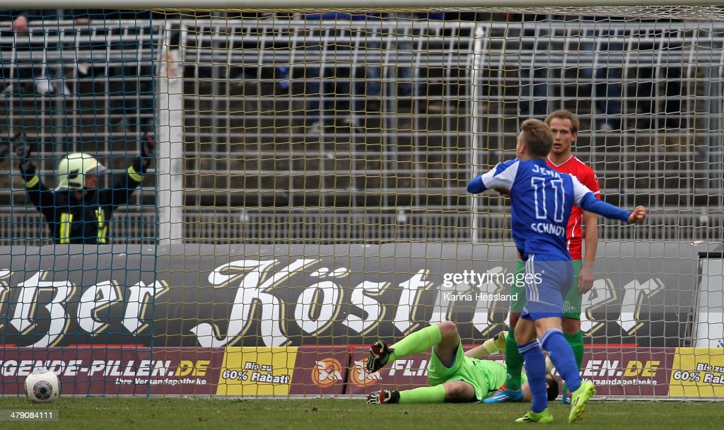 Tino Schmidt of Jena scores the second goal, Goalkeeper Matthias Tischer of Magdeburg without a chance during the Regionalliga match between FC Carl Zeiss Jena and 1.FC Magdeburg at Ernst Abbe Sportfeld on March 16, 2014 in Jena, Germany.