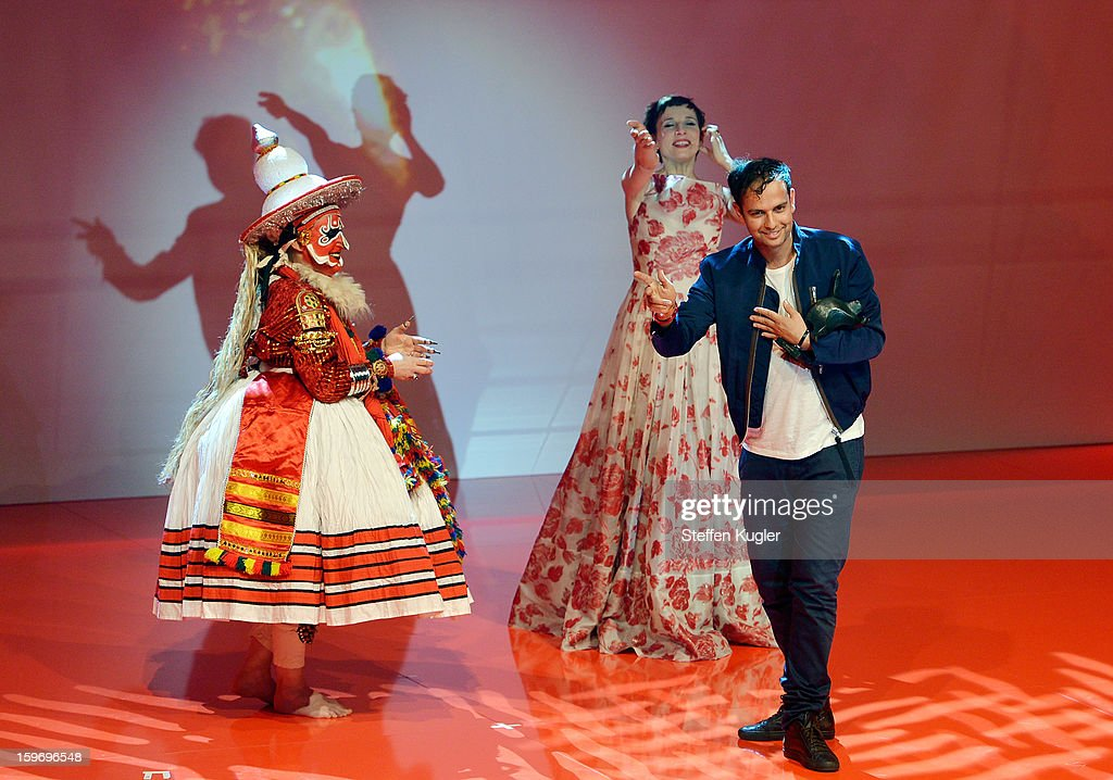 Tino Sehgal (R) leaves the stage surrounded by a traditional dancer and moderator Meret Becker (C) after receiving the B.Z. Kulturpreis on January 18, 2013 in Berlin, Germany.
