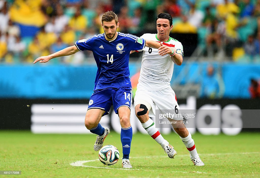 Tino Sven Susic of Bosnia and Herzegovina and Javad Nekounam of Iran compete for the ball during the 2014 FIFA World Cup Brazil Group F match between Bosnia-Herzegovina and Iran at Arena Fonte Nova on June 25, 2014 in Salvador, Brazil.