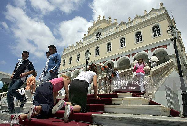 Crawling on their hands and knees in suppliance Greek Orthodox pilgrims inch towards the Church of the Virgin on the island of Tinos in this picture...