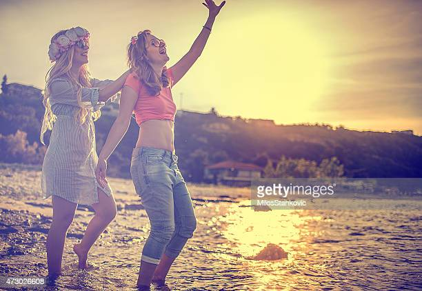 Tinted photo of two woman laughing and dancing on the beach