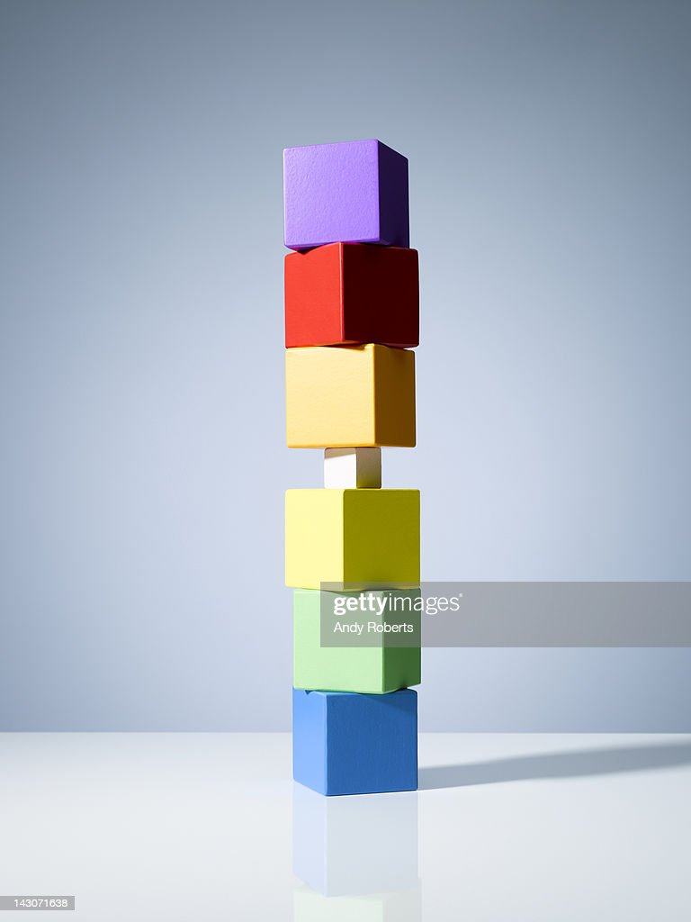 Tiny block in stack of colorful cubes : Stock Photo