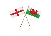 Tiny English and Welsh flag pair on gold sticks. Flag pair is standing on a reflective surface. Isolated on white background. With clipping path.