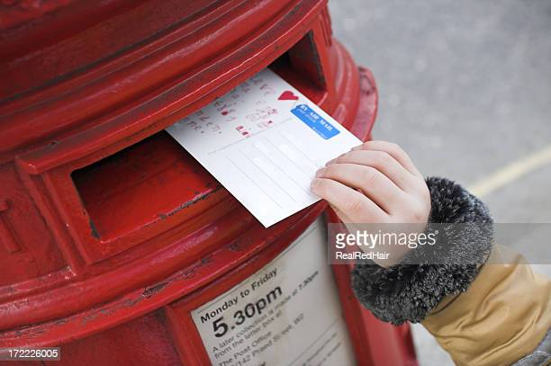 Tiny hand pushing a postcard inside a postbox
