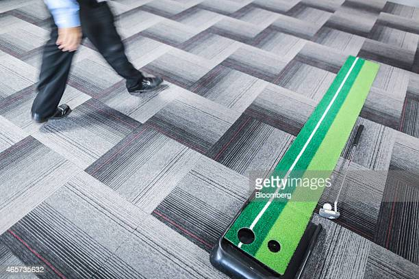 A Tiny Owl employee walks past an office minigolf game inside the company's head office in Mumbai India on Monday March 9 2015 Tiny Owl is a...