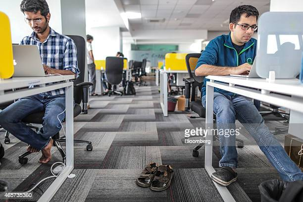 Tiny Owl employees work on laptop computers as pair of sandals sit on the floor inside the company's head office in Mumbai India on Monday March 9...