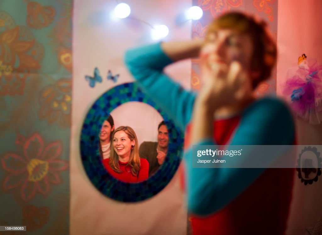 A tiny public is reflected in a mirror on the wall as actress Aixa Villagran performs during her 'Manual de orgasmos fingidos' micro theater show at the 'Micro Teatro por Dinero' on December 15, 2012 in Madrid, Spain. In November 2009, fifty artists presented a theatre project in the thirteen rooms of a former brothel, two weeks before its demolition, with each function lasting less than 10 minutes. The initiative was a huge success, with more people queueing up outside than could enter. Today's 'Micro Theatre For Money' is named after the former brothel on Ballesta Street, and offers a cheap and original way for going out at night, especially in times of financial hardship. With each show priced at 4 Euros, over 150,000 spectators have already attended performances at the tiny theatre in the Malasana area. Anyone can submit a project to be chosen to perform for a month in one of the five tiny rooms in the basement of the theatre, making it an ideal platform for young Spanish authors and actors, often unemployed, to perform.
