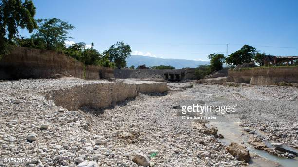 PortauPrince Haiti December 09 2012 A tiny river is flowing trough a mostly dry river bed And a seemingly destroyed bridge is visible in the...