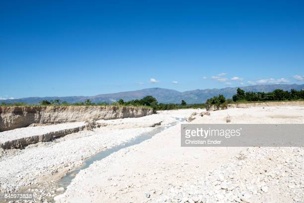PortauPrince Haiti December 09 2012 A tiny river is flowing trough a mostly dry river bed mountains can be seen in the background
