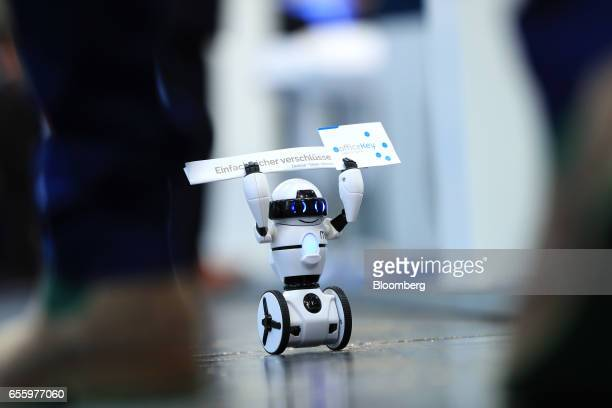 A tiny WowWee Group Ltd Coder MiP programmable balance robot carries company business cards through an exhibition hall as a promotional device at the...
