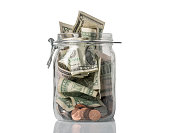 A tip jar or jar for savings filled over the top with American coins and bills.