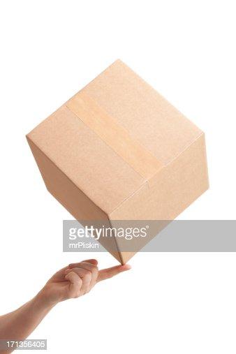 Tip of cardboard box balancing on fingertip