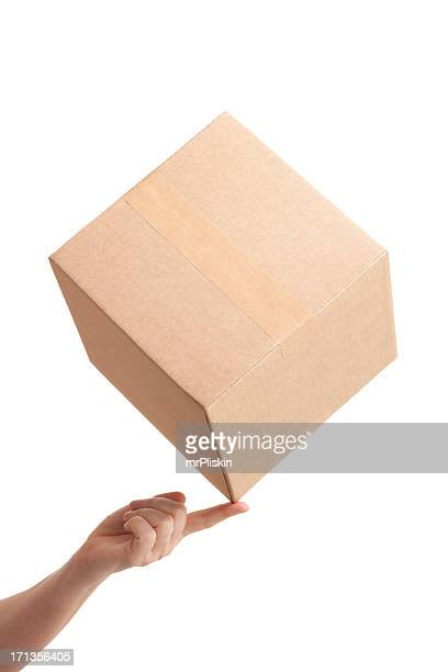 Tip of cardboard box balancing on fingertip
