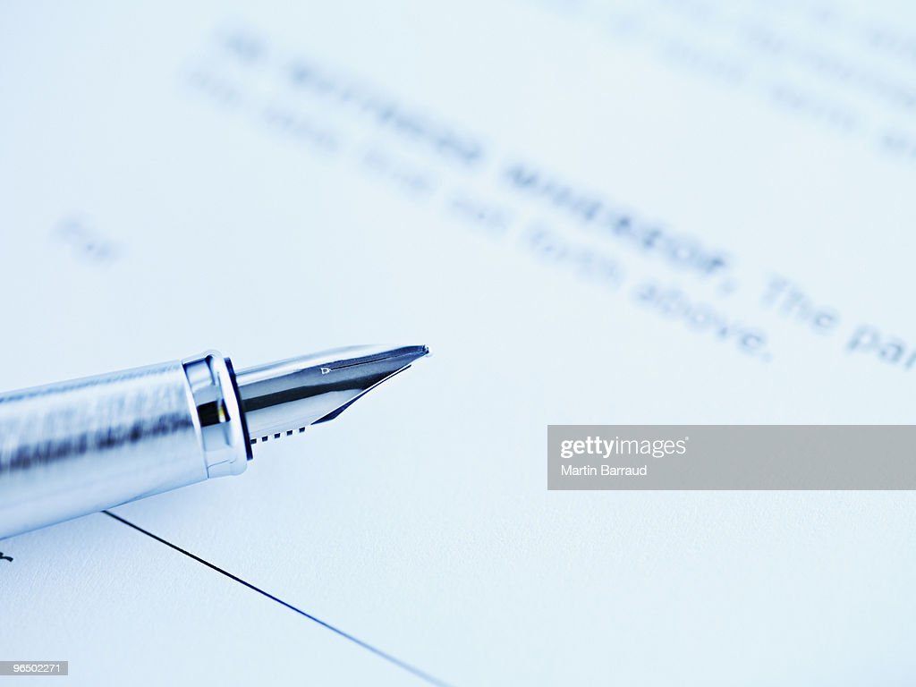 Tip of fountain pen laying on paper : Stock Photo