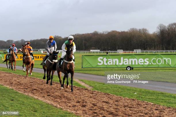 Tippering ridden by Henry Oliver lead the runners and riders to the start of the Play Online Now At StanJamescom Casino Handicap Hurdle