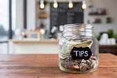 """Foreground focus is on a glass jar labeled """"tips"""" in chalk.  The jar is sitting to one side on a rustic wooden table, full of coins and bills, with coffee shop scenery in the background."""