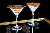 Beautiful tiramisu served in a glass with chocolate sticks on a black background. Pair of glasses.
