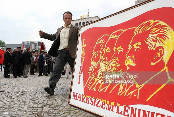 A handful of Albanian communist nostalgics hold banners showing from left Karl Marx Frederick Engels the founder of the Soviet Union Vladimir Illich...