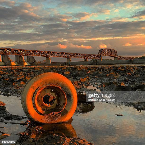 Tire And Bridge Against Cloudy Sky During Sunset