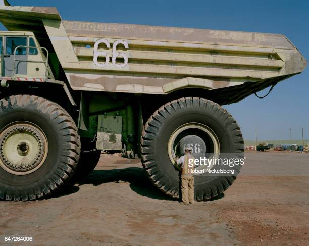 A tire mechanic checks the air pressure on 12foot diameter tires of a 200ton truck at the Buckskin Coal Mine 12 miles north of Gillette Wyoming June...