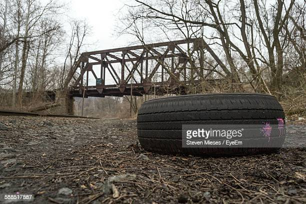 Tire On Field With Bridge In Background