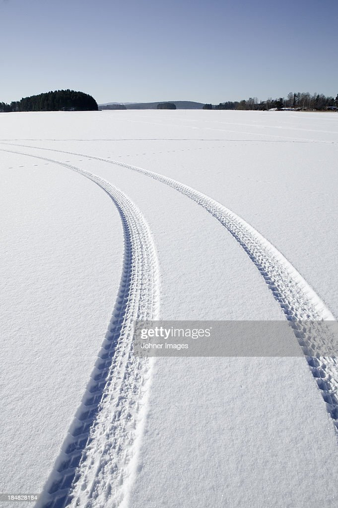 Tire track on snowy landscape