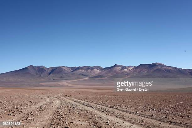 Tire Tracks Leading Towards Mountains Against Clear Blue Sky