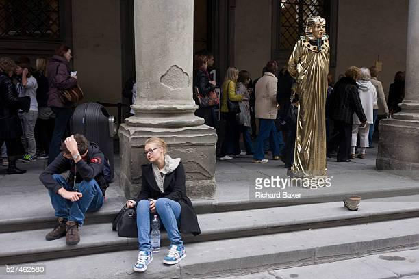 Tired and disappointed tourists and a pretend Egyptian pharaoh busker stand awaiting custom in Florence's Piazza degli Uffizi In the darker covered...