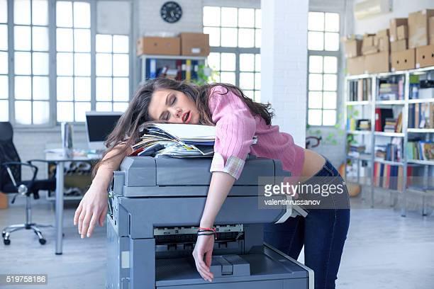 Assistant fatigué dormir sur un photocopieur