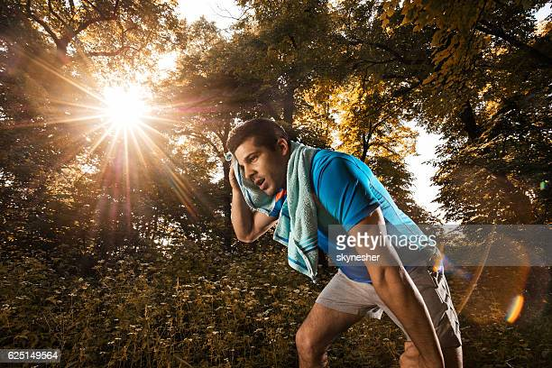 Tired athlete wiping sweat with towel after exercising in nature.