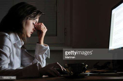 Tired business person with headache working at night : Stock Photo