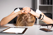 Tired business woman resting her head on desk