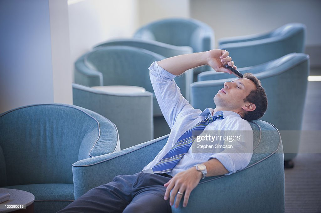 tired businessman and his cell phone : Stock Photo