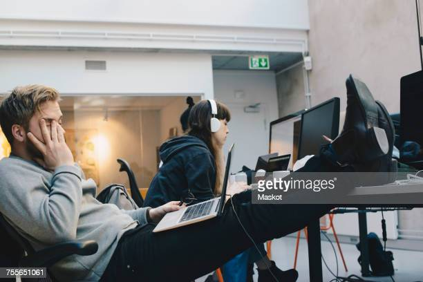 Tired computer programmer sitting with feet up on desk while colleagues working in background