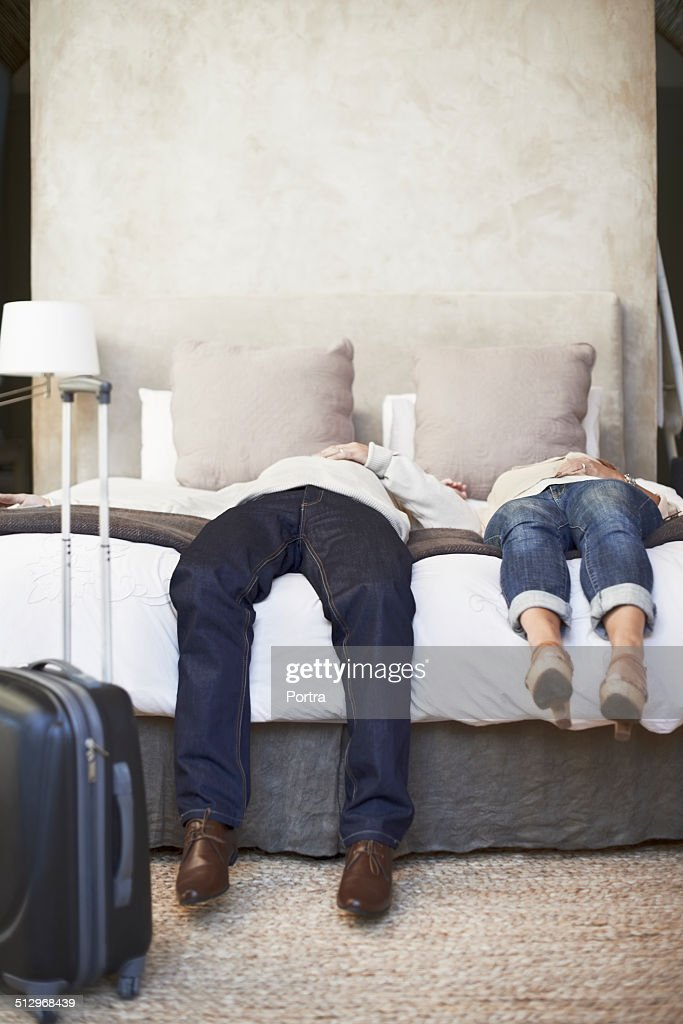 Tired couple lying on bed in hotel