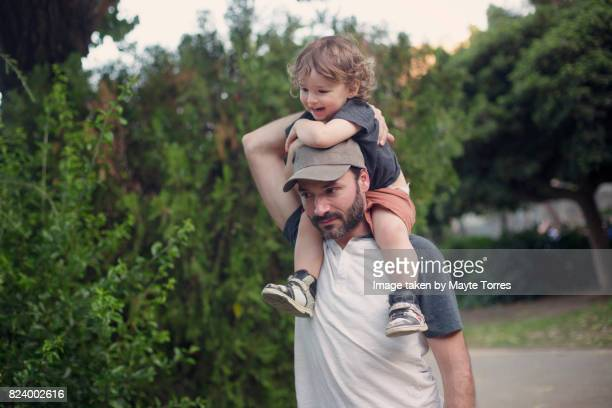 tired dad carries boy in his shoulders