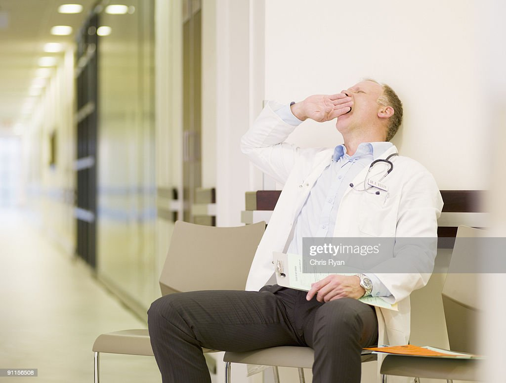 Tired doctor sitting in hospital waiting area : Stock Photo