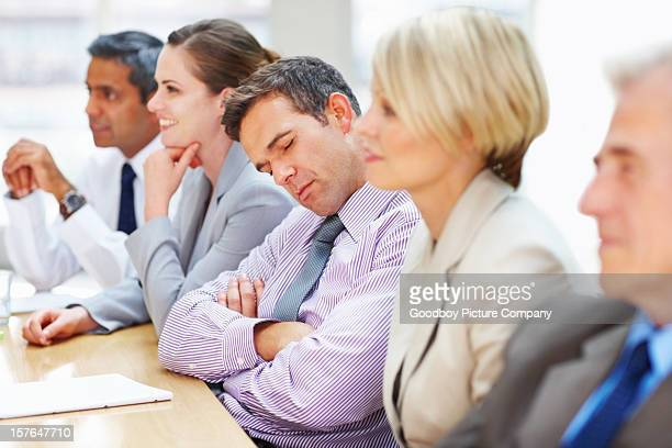 Tired executive falls asleep during a business meeting